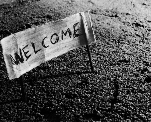 """""""Welcome"""" written on a piece of fabric, attached to a stick at either end with the sticks in the ground to create a sign"""