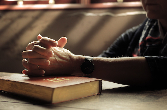 hands folded as if in prayer sitting on top of a Bible with light streaming through a window in the background