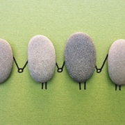 4 flat oval-shaped stones sitting next to each other vertically on a piece of paper with feet and hands holding each other drawn in