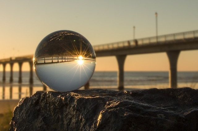 clear glass globe on a rock in front of a pier going out into an ocean, the pier and sky inverted in globe