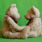 two teddy bears with handkerchiefs seated facing each other