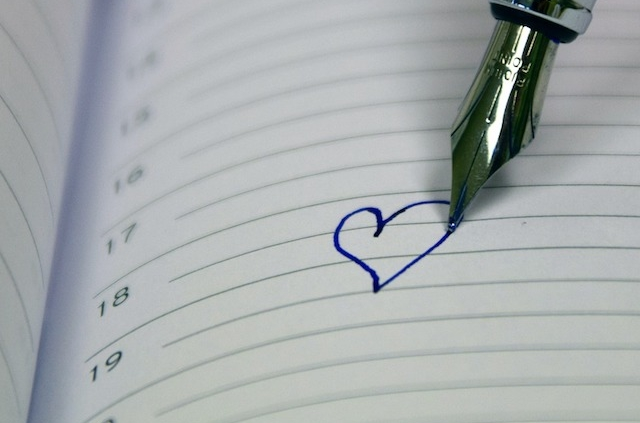 calendar page with a fountain pen drawing a heart on it