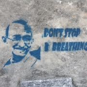 """graffiti on wall of gandhi's head and text that says """"Don't Stop Breathing"""""""