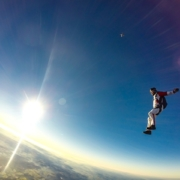 man free-fall sky diving with sun in background