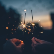 two hands holding lit sparklers at dusk