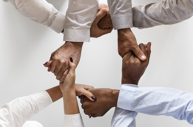 4 people holding hands, each pair of hands crossed and holding hands of person next to them in a circle