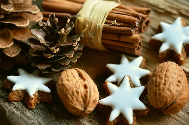 a bundle of cinnamon sticks tied with twine, surrounded by pine cones, walnuts in the shell and small frosted star-shaped cookies