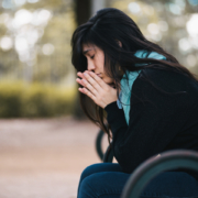 woman wearing a coat and scarf, sitting on a bench praying