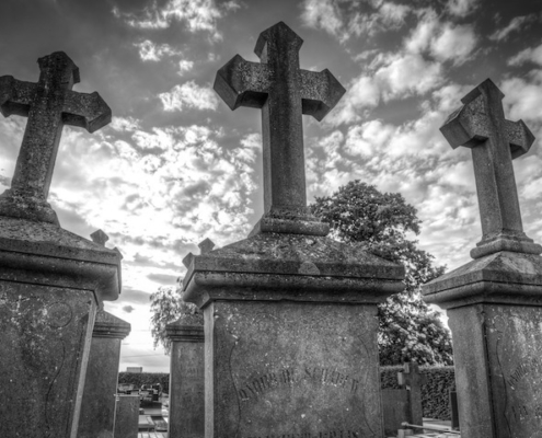 3 old gravestones with crosses on top and sun shining through the clouds in the background
