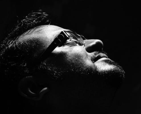 man in glasses looking upward - just his face in shadows