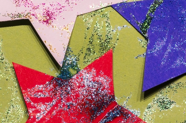 paper stars with glitter tossed over them