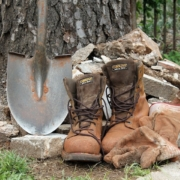 work boots, a pointed shovel and work gloves alongside a tree trunk and stone rubble